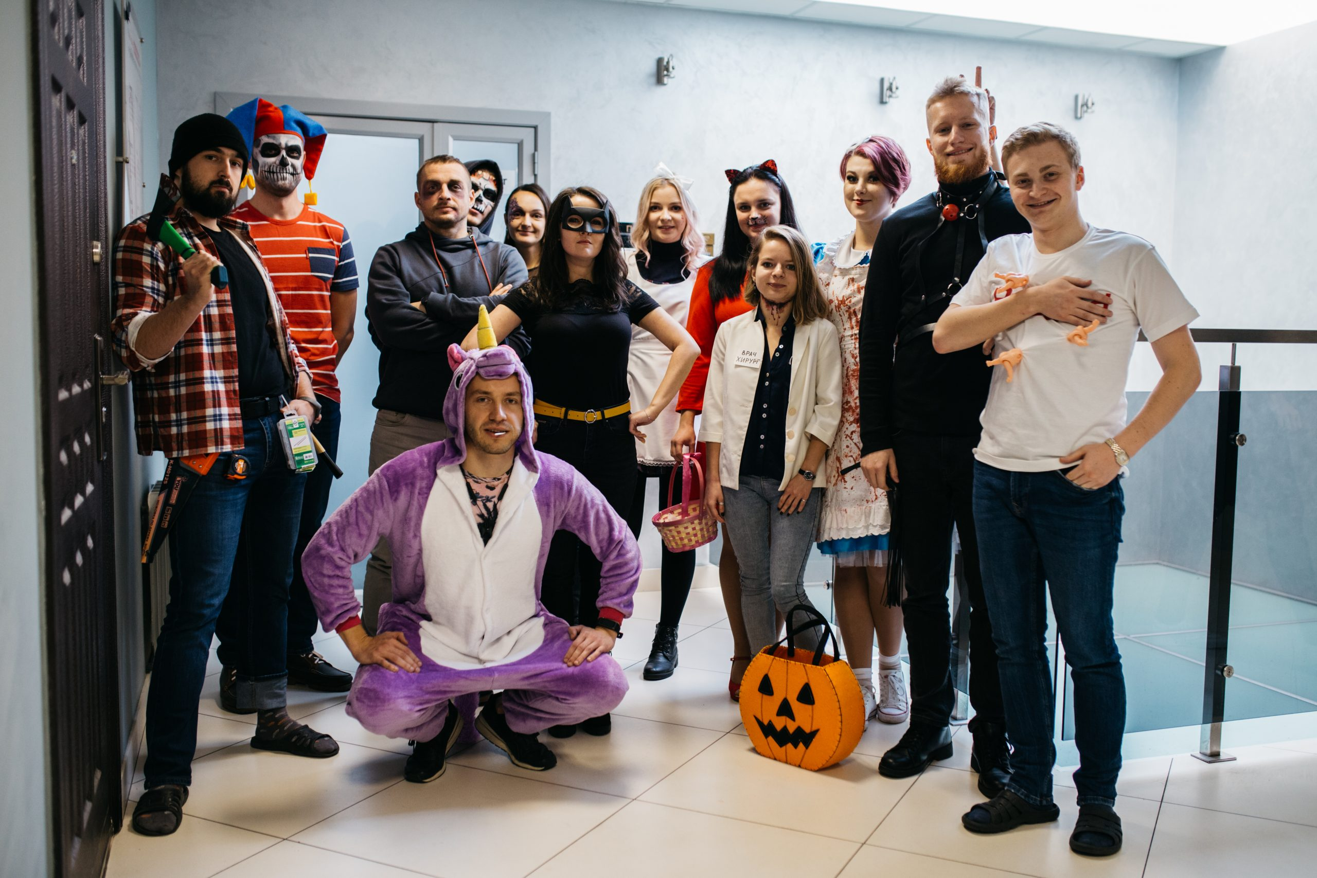 Smart IT team in creative Halloween outfits at the office